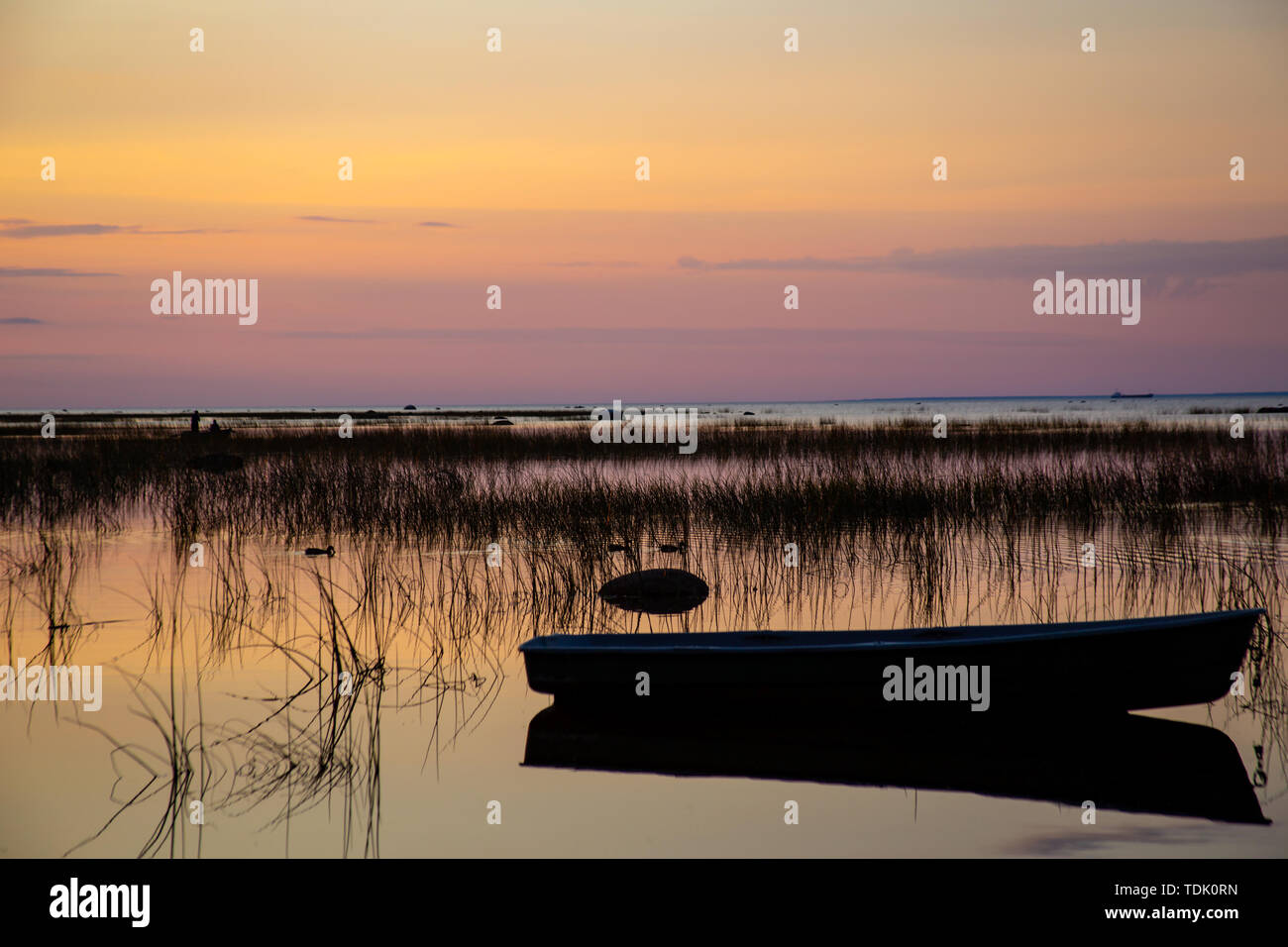 Silhouette of a fishing boat at anchor, reflected in the calm and clear water of the lake, covered with sedge at dusk against the background of a beautiful multi-colored sunset sky. - Stock Image