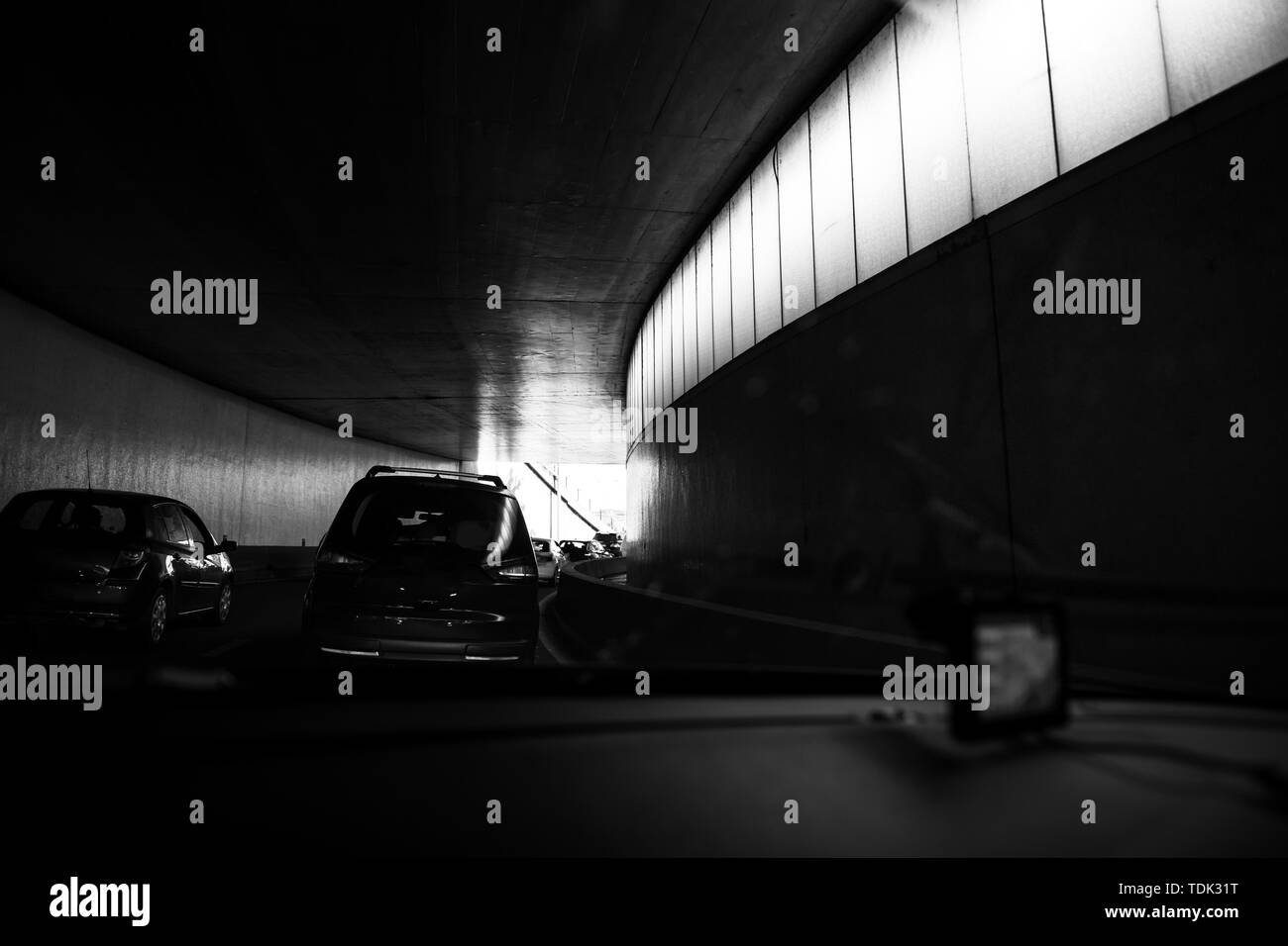 Driver POV point of view personal perspective at the traffic jam rush hour front driving cars inside the tunnels of Paris Peripherique ring road black and white. - Stock Image