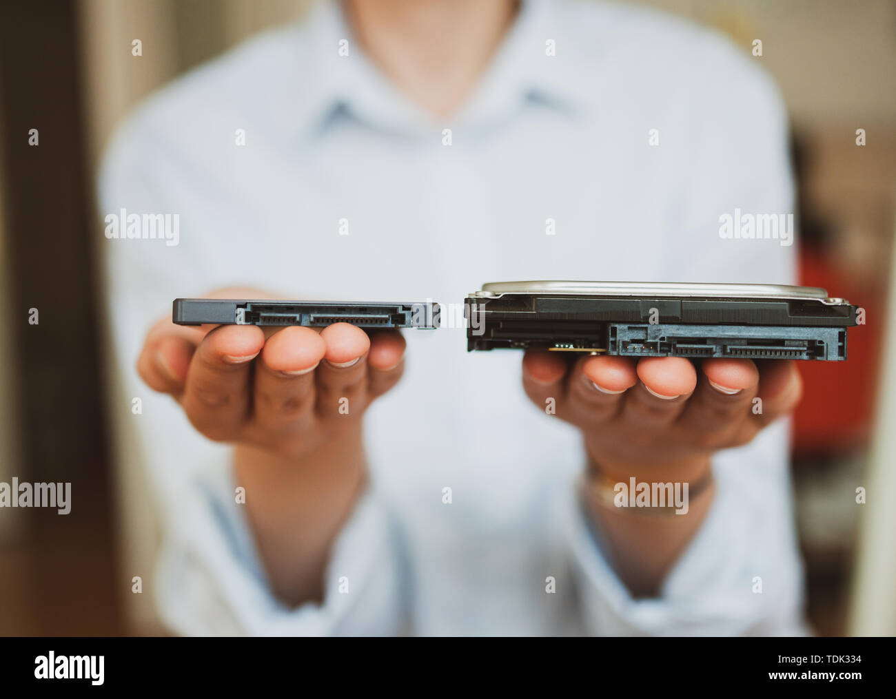IT woman holding presenting two different generations of computer disks HDD hard disk drive and SSD solid state drive - offering them to viewer - Stock Image