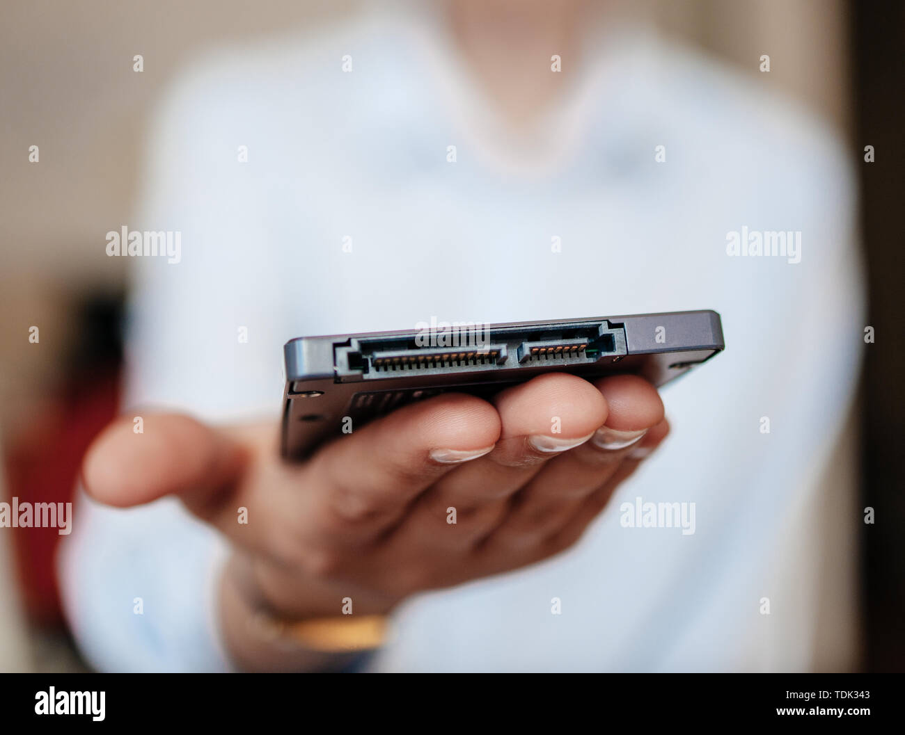 Woman presenting demonstrating holding in palm new small fast SSD 4tb 10tb computer disk drive with SATA connectivity - Stock Image