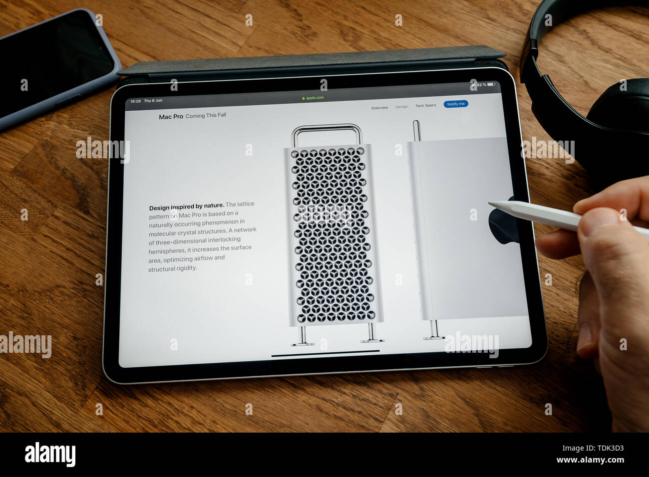 Paris, France - Jun 6, 2019: Man reading on Apple iPad Pro tablet about latest announcement of at Developers Conference WWDC - showing the Mac Pro workstation with design inspired by nature text - Stock Image
