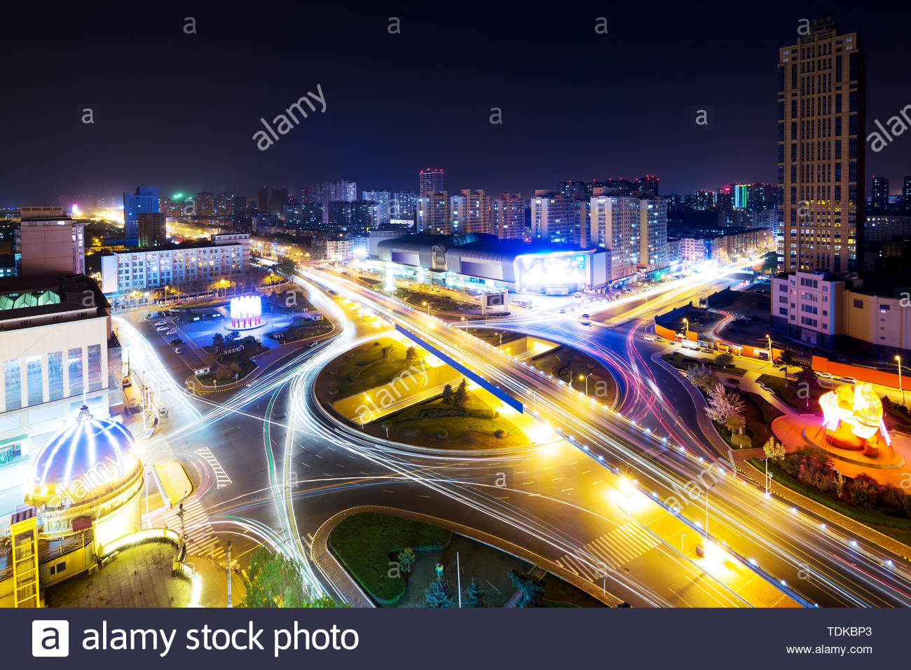 night scene of busy traffic on elevated road in midtown of modern city - Stock Image