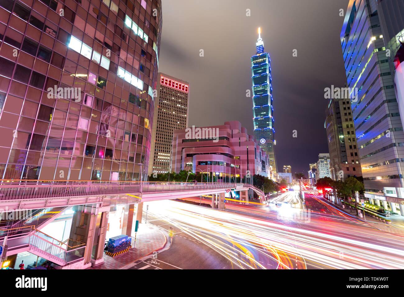Busy traffic light trails in modern street and illuminated landmark of taipei at night Stock Photo