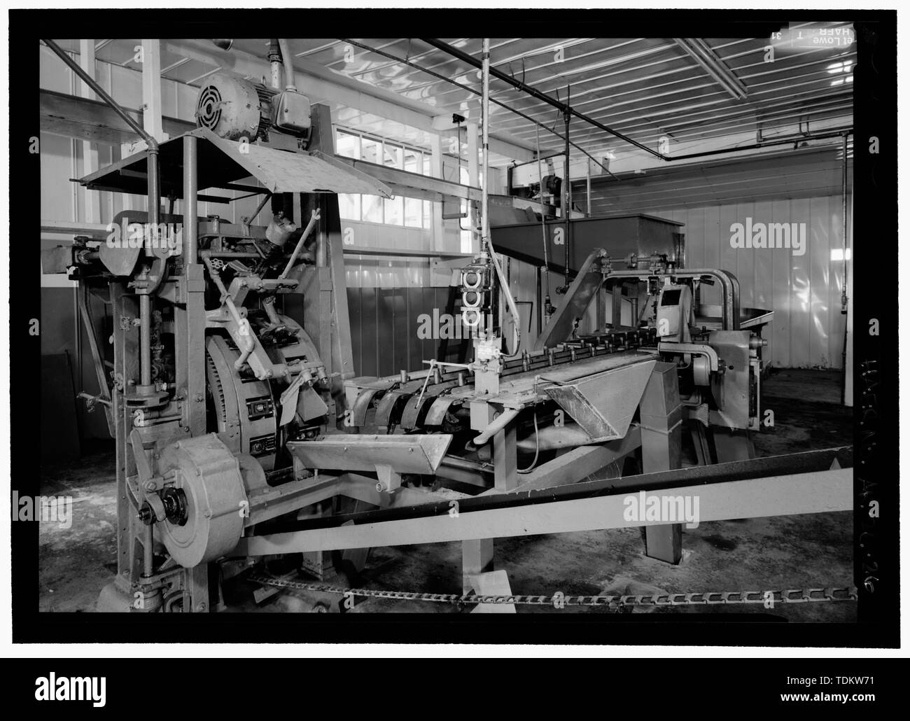 Oblique shot of chink; looking at chain fish conveyor and feed through into machine - Kake Salmon Cannery, 540 Keku Road, Kake, Wrangell-Petersburg Census Area, AK - Stock Image