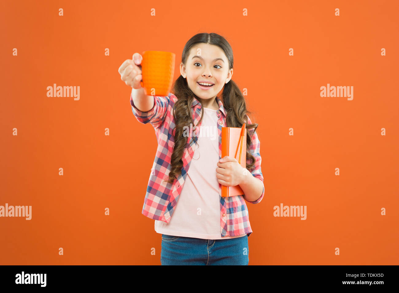 Help yourself. Cute schoolgirl enjoying school break on orange background. Little girl having tea break. Small child holding book and cup at meal break. Its break time. Stock Photo