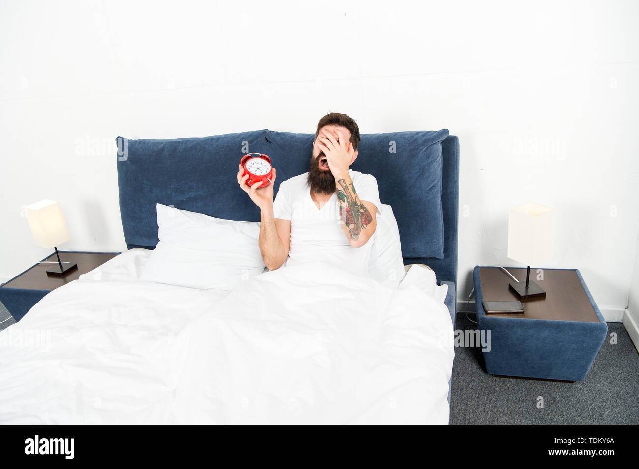 Man bearded hipster hate wake up early. Destructive energy. Hardest moment of day. It is totally normal to hate your alarm sound. Hateful schedule. Best alarm clocks for people who hate mornings. - Stock Image