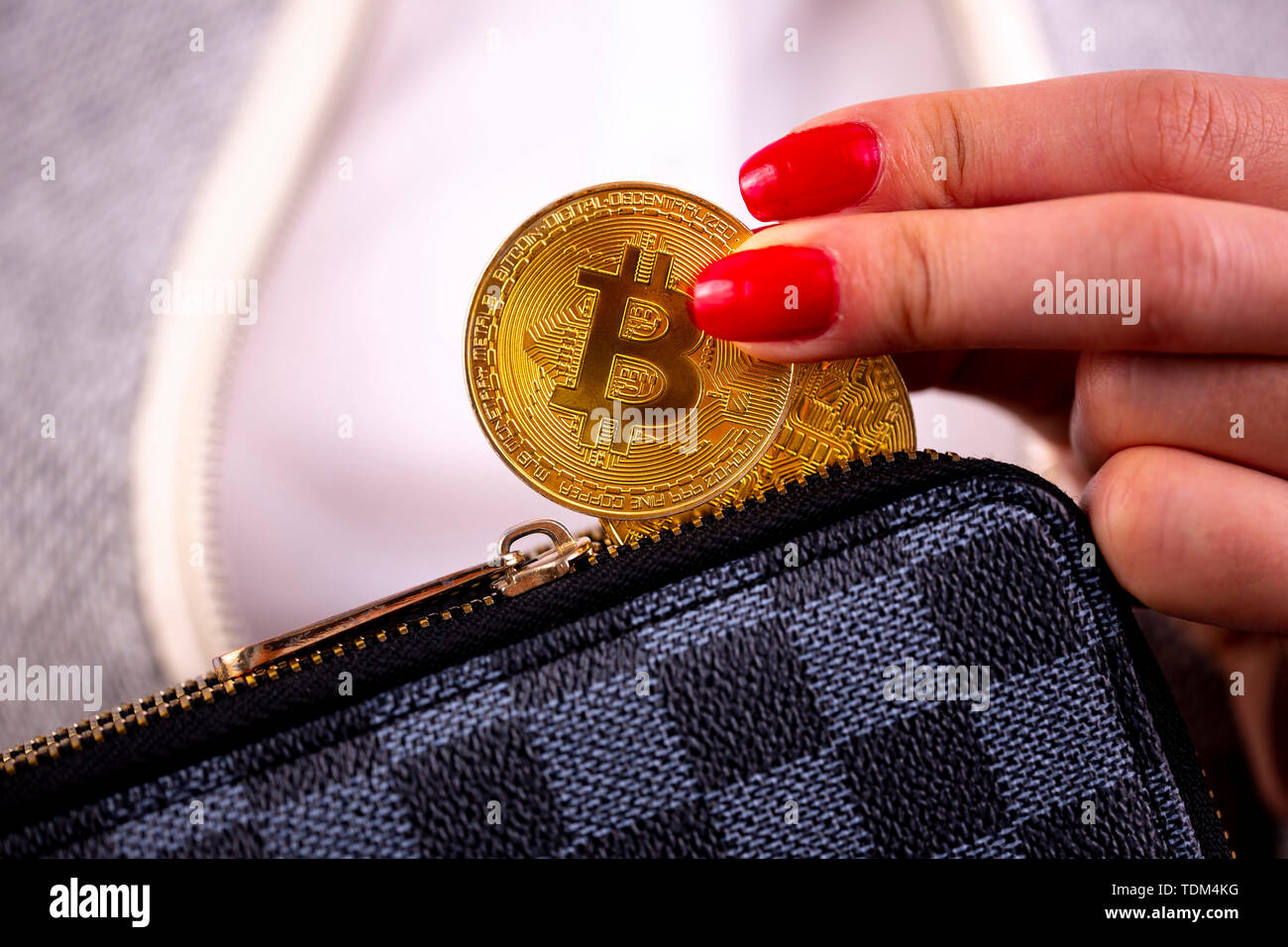 Virtual cryptocurrency money Bitcoin golden coins in the left hand of a woman with red nail polish and a purse. The future of money. Stock Photo
