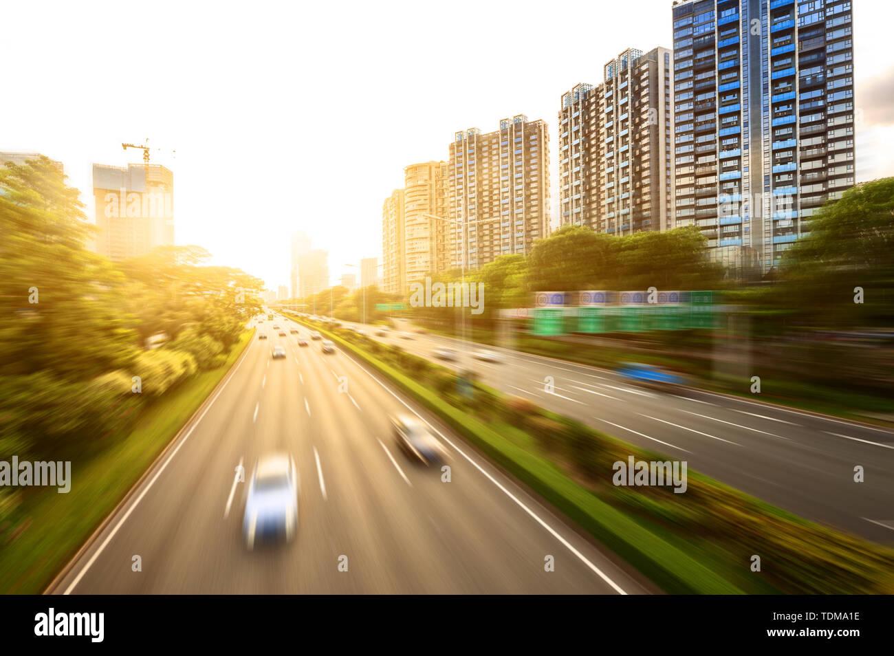 busy asphalt road in modern city under twilight - Stock Image