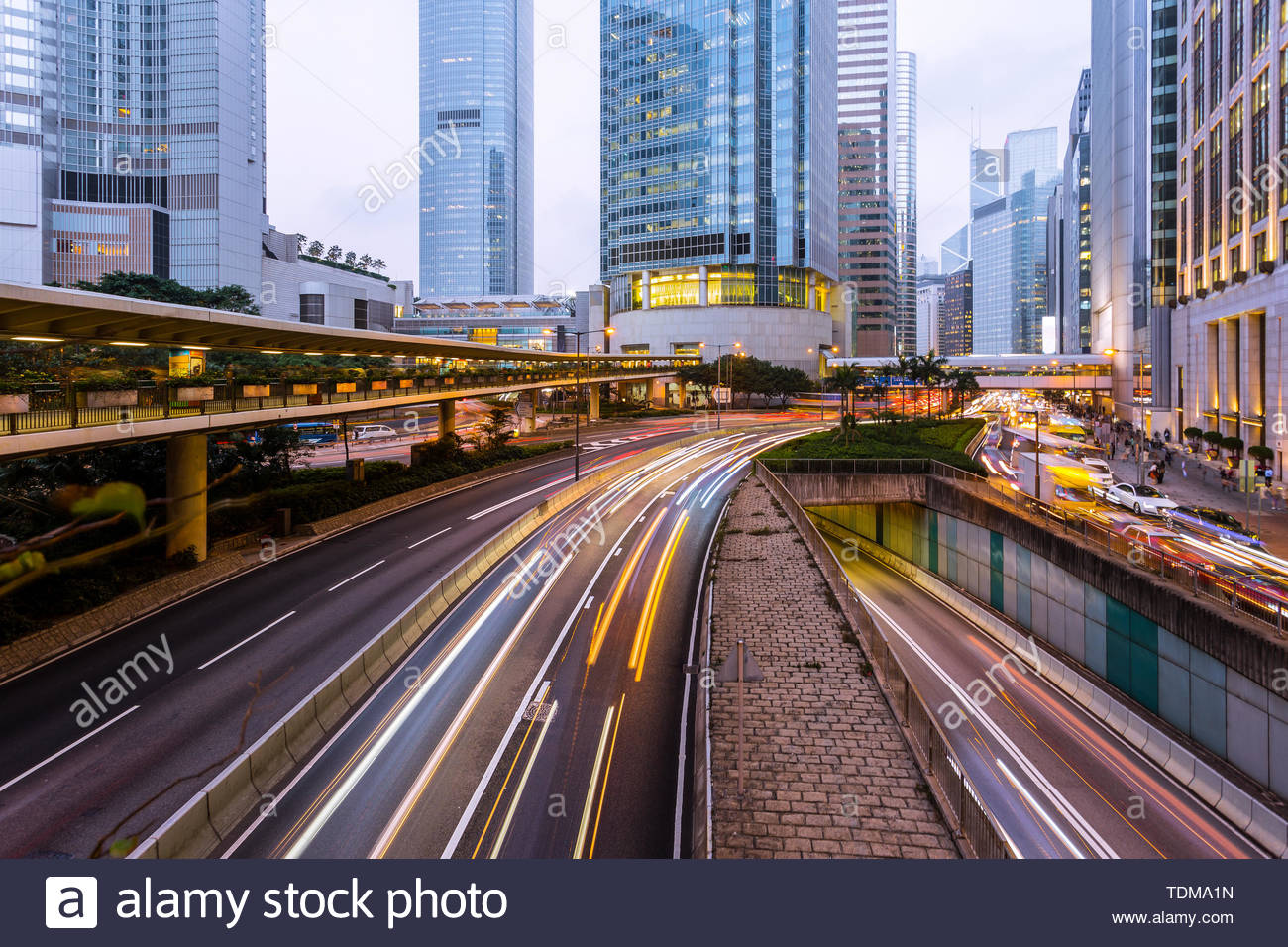 Busy traffic light trails and office buildings. - Stock Image
