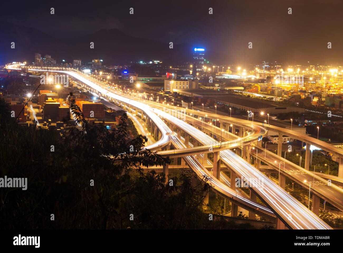 Illuminated and elevated expressway and cityscape at night Stock Photo