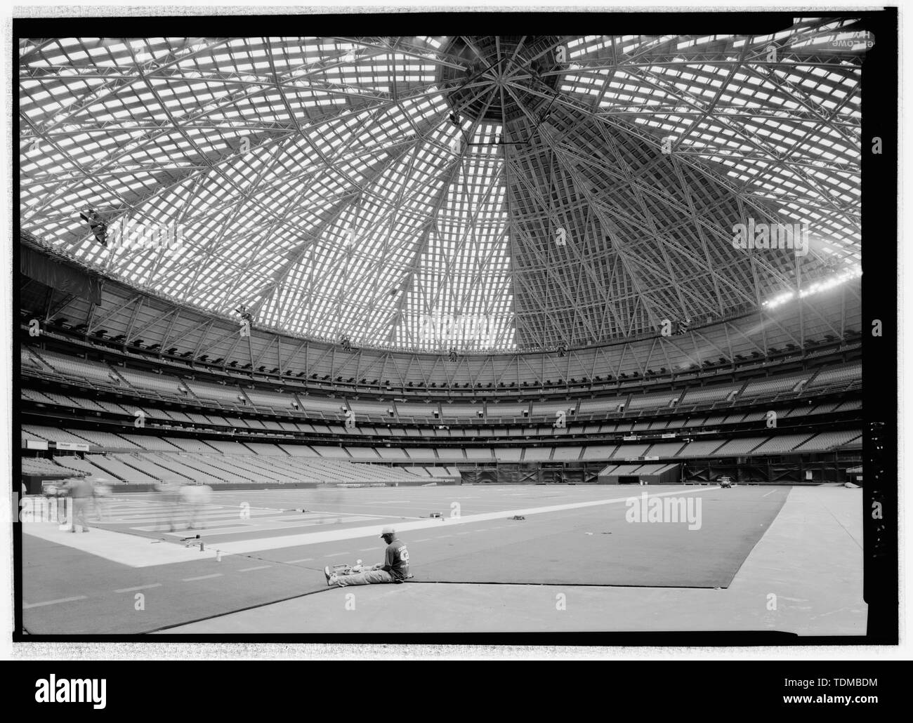 PERSPECTIVE LOOKING SOUTHWEST FROM FIELD LEVEL. WORKER IN FOREGROUND IS STITCHING TOGETHER ASTROTURF FOR FOOTBALL GAMES. - Houston Astrodome, 8400 Kirby Drive, Houston, Harris County, TX; Lloyd and Morgan; Wilson, Morris, Crain and Anderson; H A Lott, Inc; Eyster, Herbert H; Sam P Wallace Company; Fish Electric; The Prescon Corporation; Walter P Moore and Associates, Inc; Praeger-Kavanagh-Waterbury; Turney, J G; Lockwood, Andrews and Newnam Inc; Dale S Cooper and Associates; Kiewitt, G R; Bass, Louis O; Bolt, Beranek and Newman; American Bridge Division; US Steel Corporation; The Rackle Compan - Stock Image