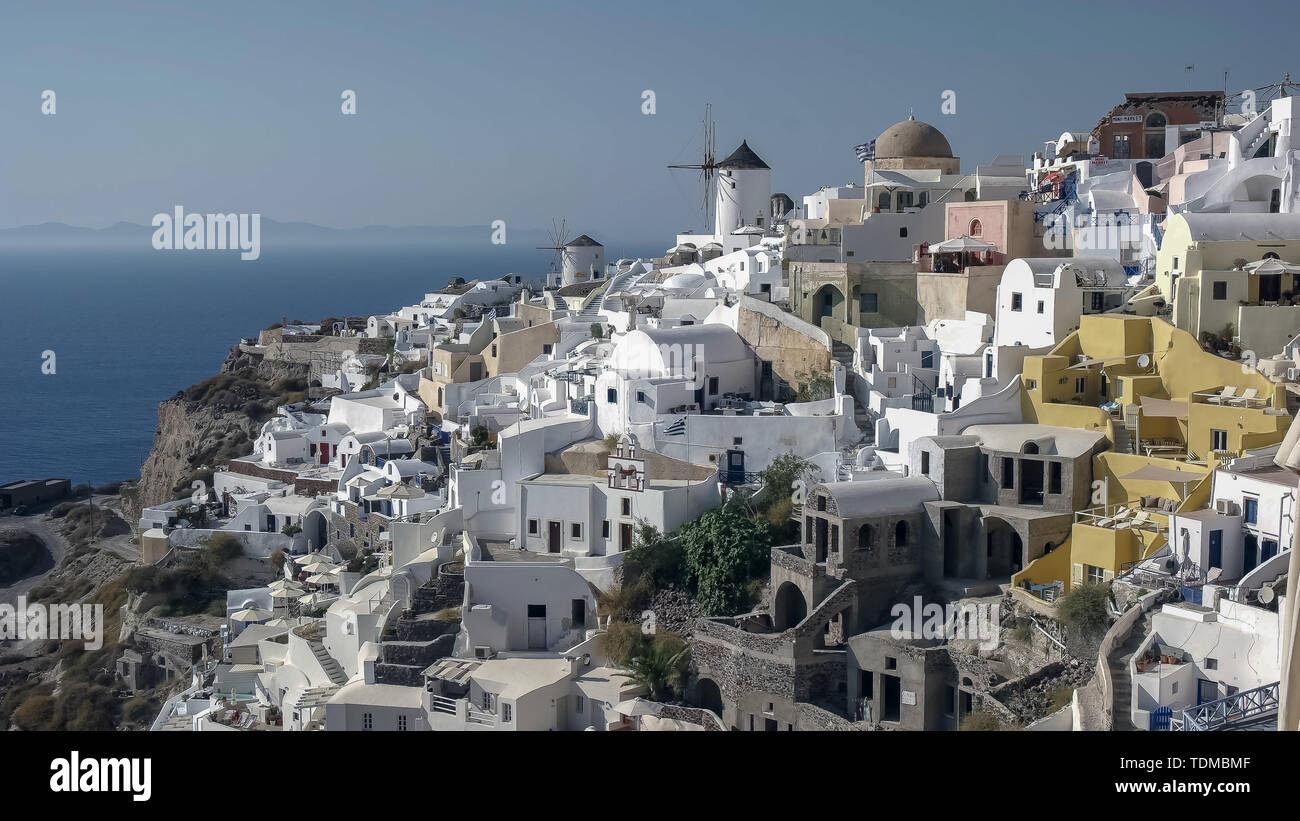 daytime wide shot of houses and windmills at oia, santorini - Stock Image