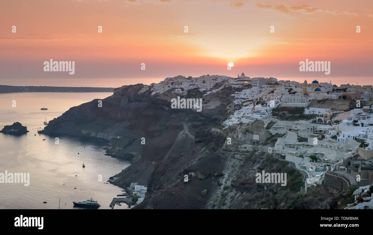 wide view of sunset and the village of oia on santorini - Stock Image