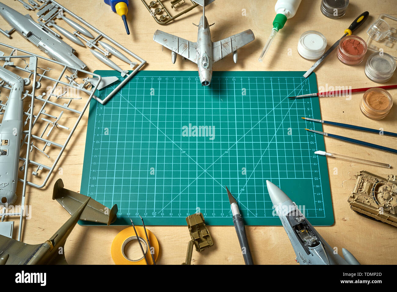Top view on plastic model scale with accessories on  green pad on bright wooden table - Stock Image