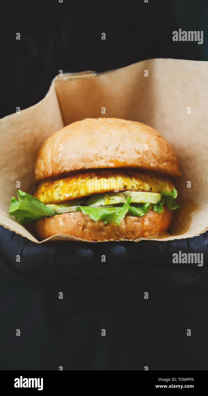 Vegan snacks - burger with text label in hands Stock Photo