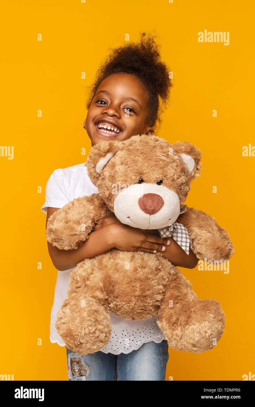 Cute african american child hugging teddy bear and smiling - Stock Image