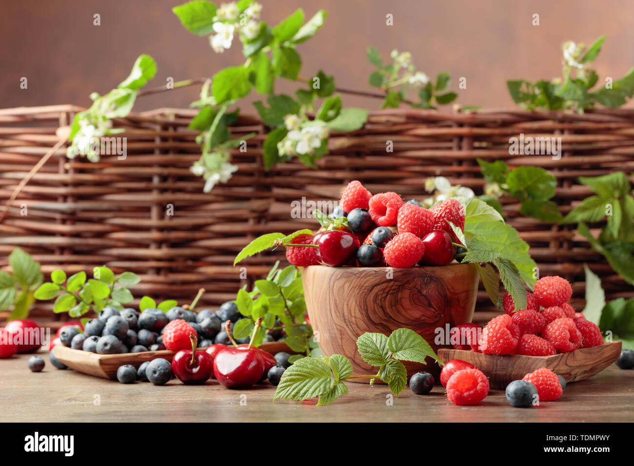 Berries closeup colorful assorted mix of strawberry, blueberry, raspberry and sweet cherry on a old wooden table in garden. Various juicy berries with - Stock Image
