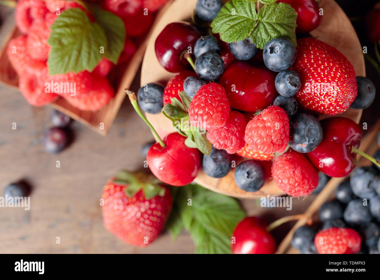 Berries closeup colorful assorted mix of strawberry, blueberry, raspberry and sweet cherry on a old wooden table in garden. Top view. - Stock Image