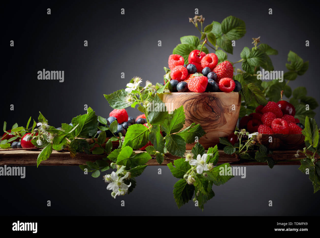 Berries closeup colorful assorted mix of strawberry, blueberry, raspberry and sweet cherry on a old wooden table. Various juicy berries with leaves. - Stock Image