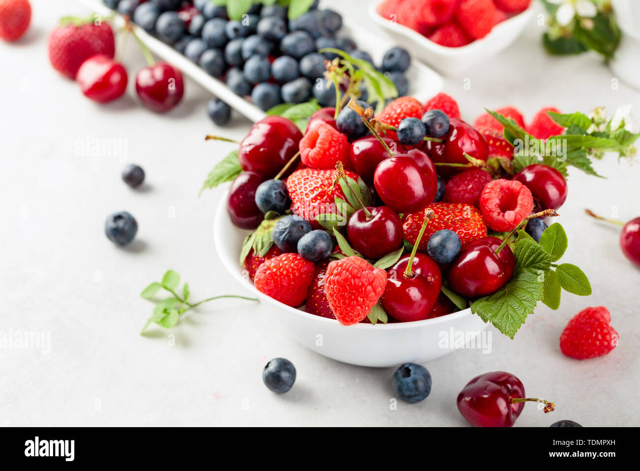 Berries closeup colorful assorted mix of strawberry, blueberry, raspberry and sweet cherry on a white table. Various juicy berries with leaves. - Stock Image