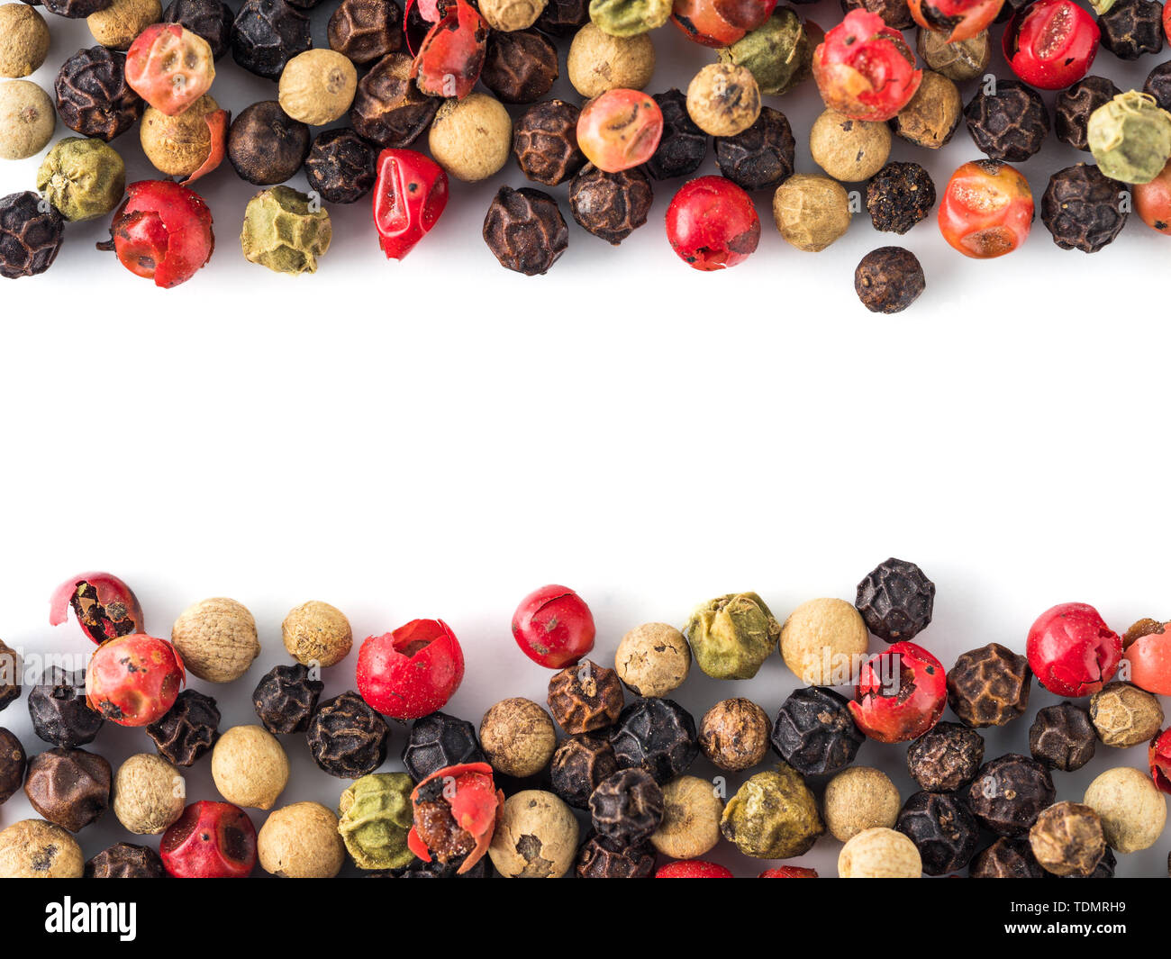 Mixed peppercorns background with white copy space in center. Food background with peppercorns. Different colored peppercorns pattern on white background, top view or flat lay - Stock Image