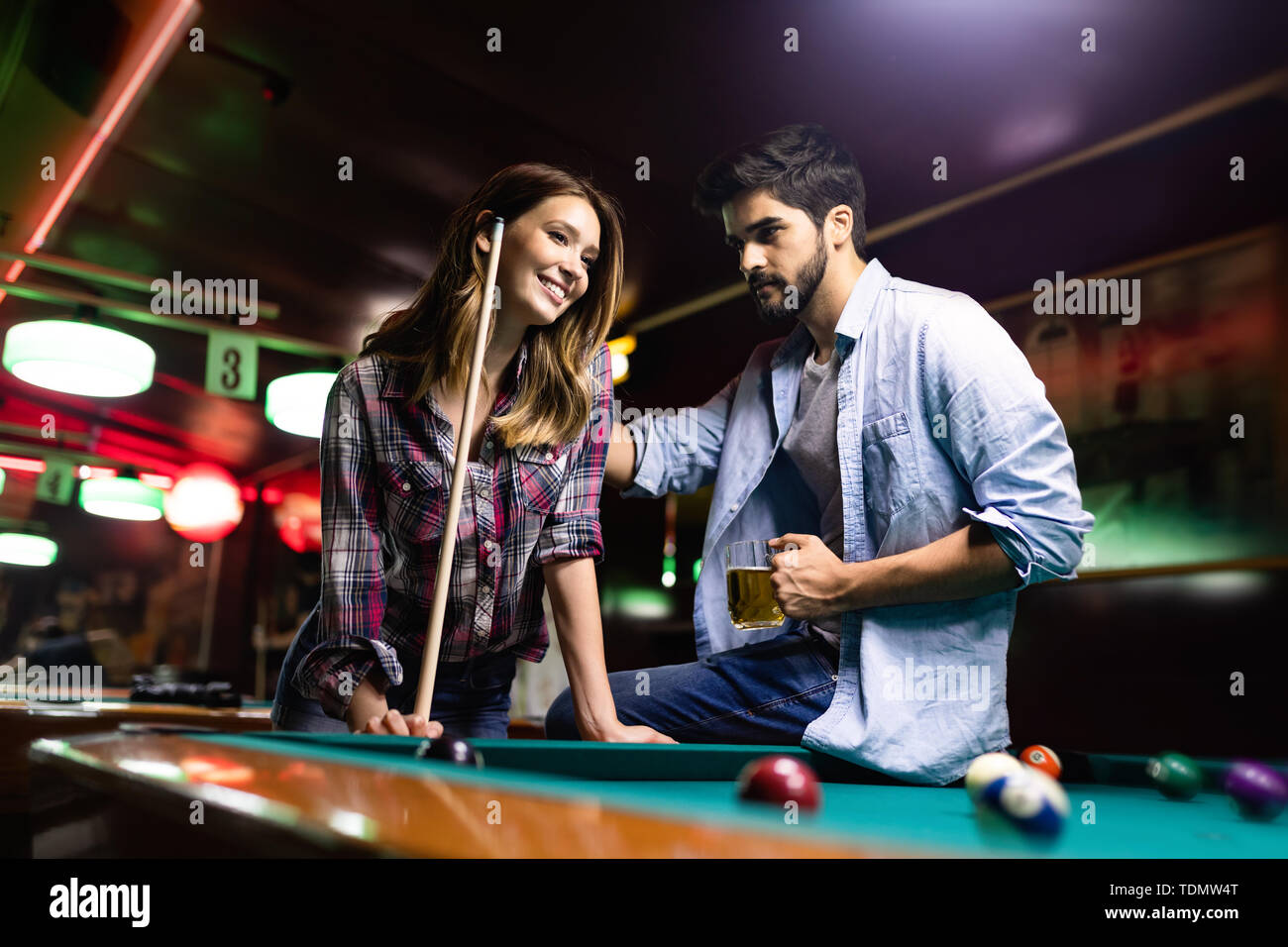Happy young man playing snooker with his girlfriend. Happy loving couple. - Stock Image
