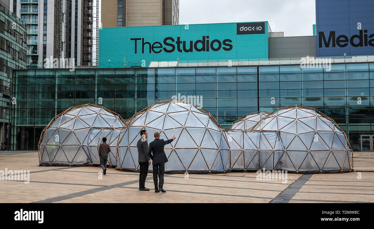 People look at Pollution Pods installed by Cleanairgm.com at MediaCityUK in Manchester. People can experience the air quality of cities across the world from clean air of Tautra in Norway and the smog and pollution of London, New Dehli, Beijing and Sao Paolo, replicated in the free airpods. - Stock Image