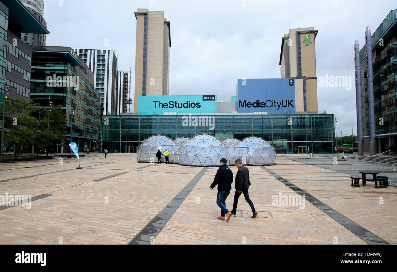 People walk past Pollution Pods installed by Cleanairgm.com at MediaCityUK in Manchester. People can experience the air quality of cities across the world from clean air of Tautra in Norway and the smog and pollution of London, New Dehli, Beijing and Sao Paolo, replicated in the free airpods. - Stock Image