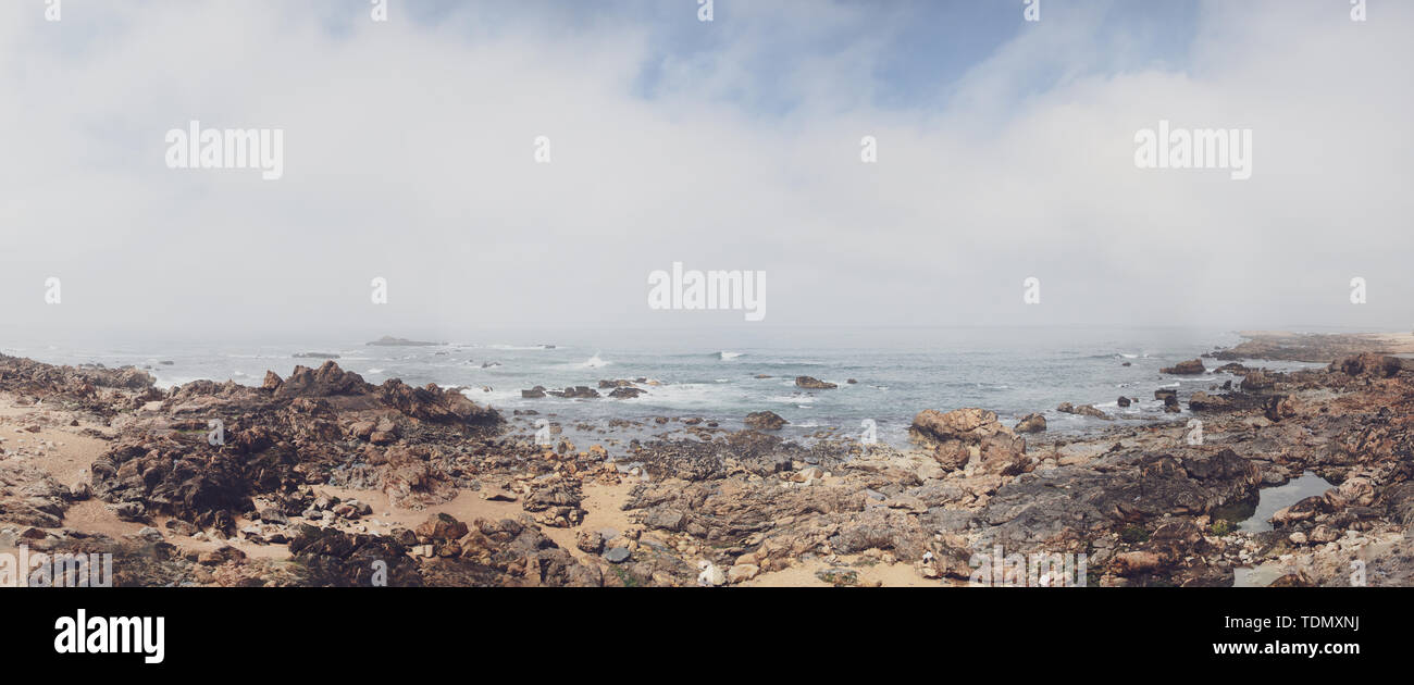 Rocky shore with a cloudy view over atlantic sea in portugal - Stock Image