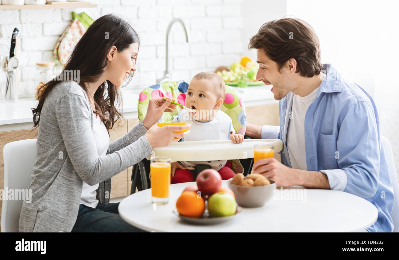 Good looking young family eating breakfast together with their baby Stock Photo