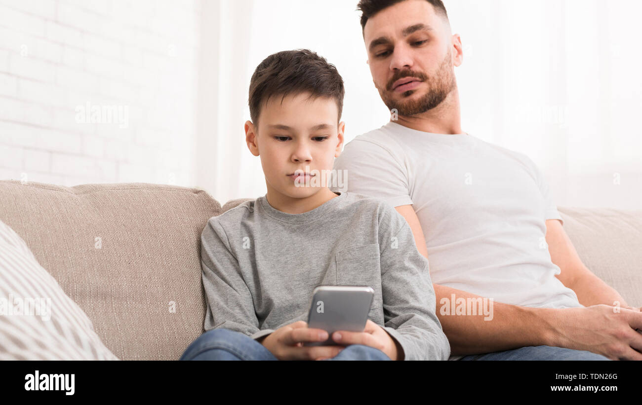Curious dad peeking at his son smartphone - Stock Image