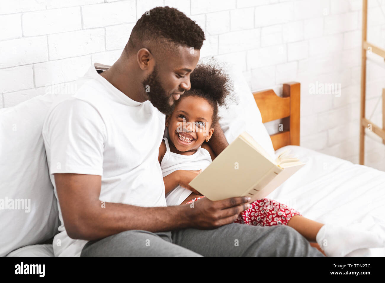 African american man reading fairy tale to his little daughter - Stock Image