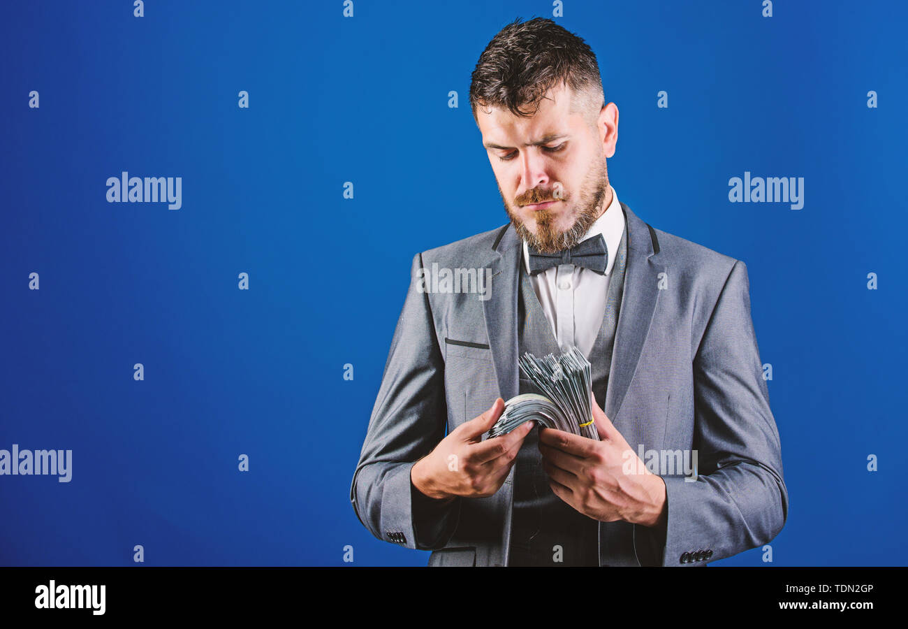 Man formal suit hold pile of dollar banknotes blue background. Businessman got cash money. Richness and wellbeing concept. Get cash easy and quickly. Cash transaction business. Easy cash loans. - Stock Image