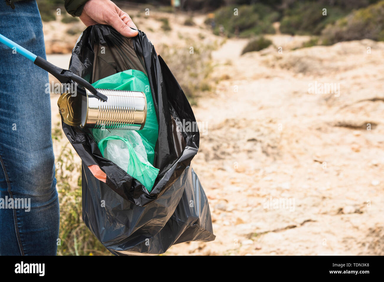 closeup of a caucasian man outdoors collecting garbage with a trash grabber stick, as an action to clean the natural environment Stock Photo