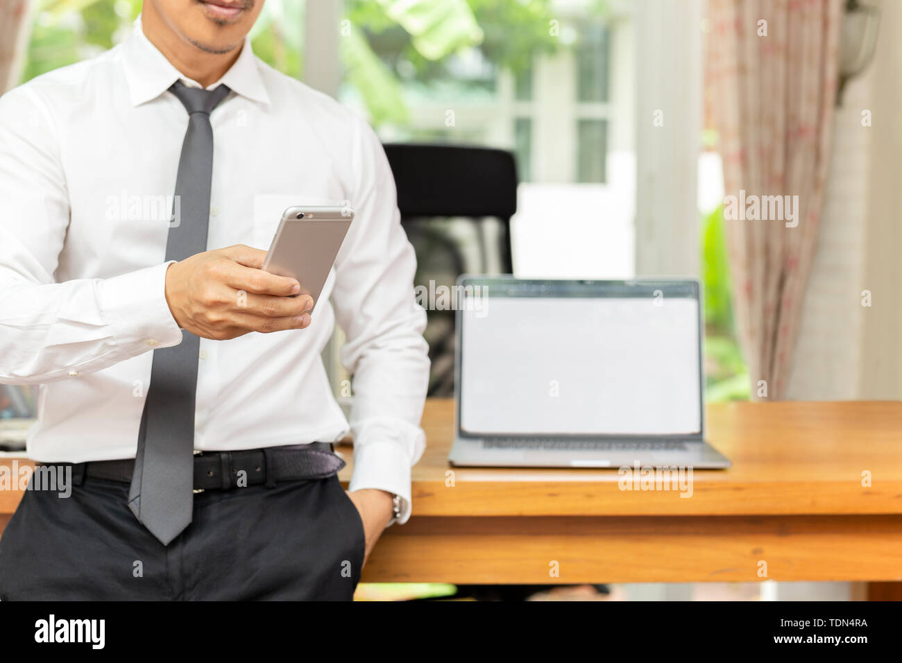 Businessman looking at cell phone with laptop on wooden table at office. Stock Photo
