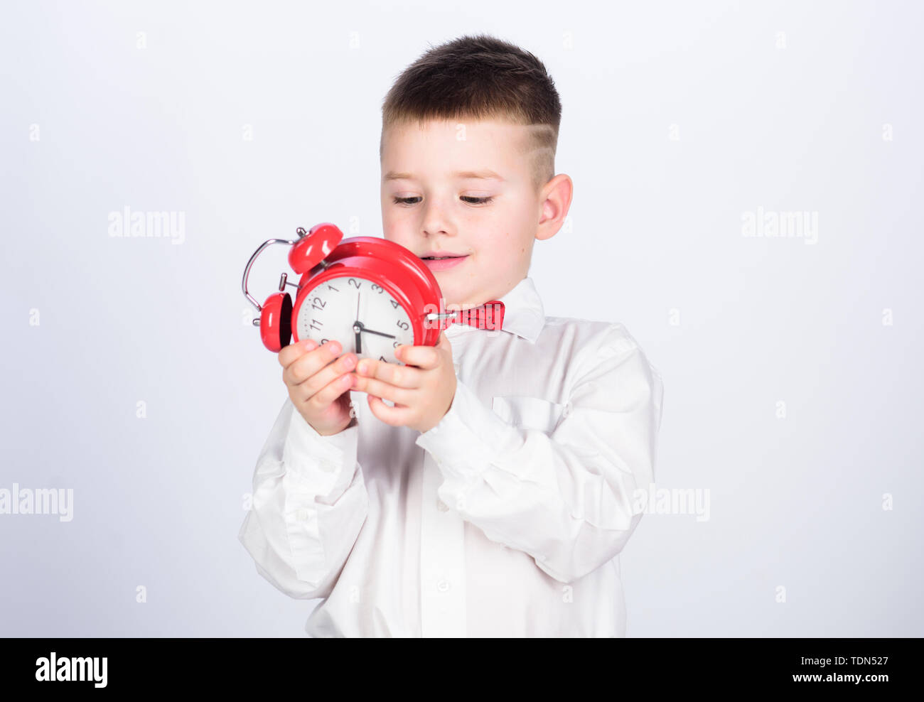 little boy with alarm clock. Time to relax. tuxedo kid. Happy childhood. Party time. Businessman. Formal wear. happy child with retro clock in bow tie. Time management. Morning. Morning vibes - Stock Image