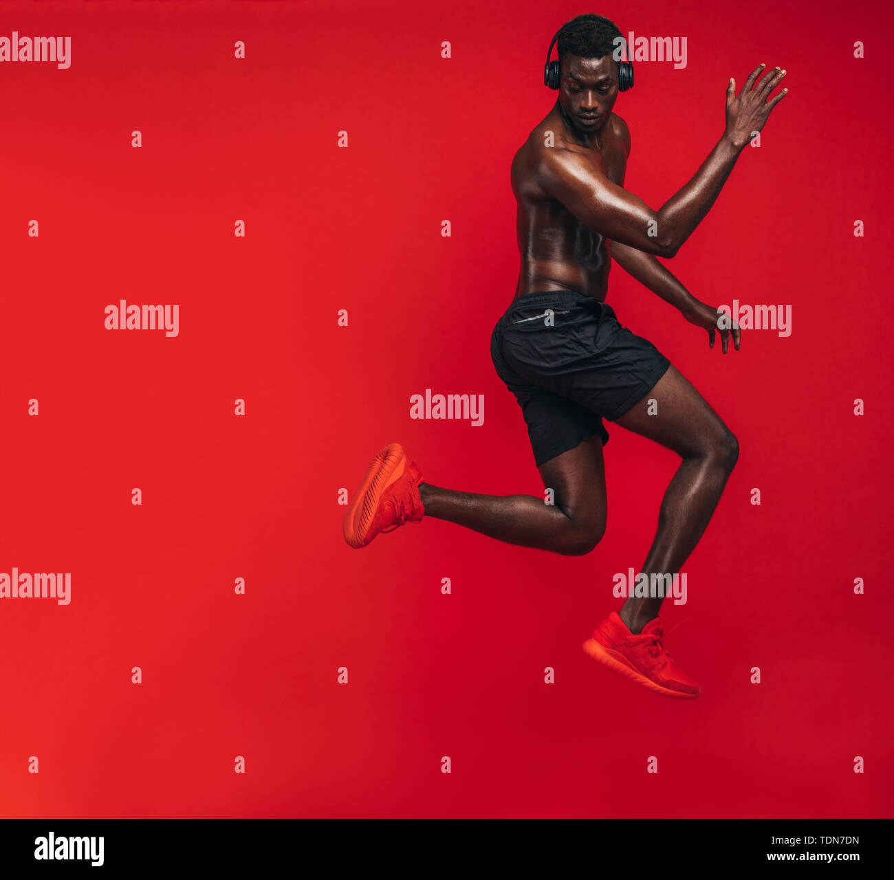 African american man with muscular body exercising on red background. Shot of a fit young man doing workout in studio. - Stock Image