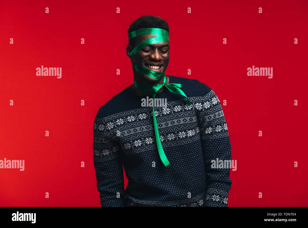 Happy african man with satin ribbon tied on his face against red background. Man wrapped as a present. - Stock Image