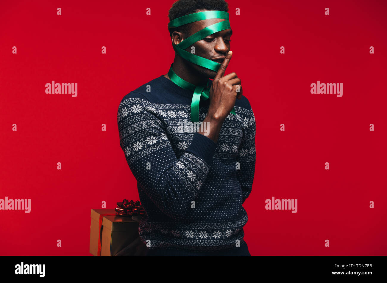 African guy wrapped in a ribbon holding a gift box and gesturing silence. Man wrapped as a gift on red background. - Stock Image