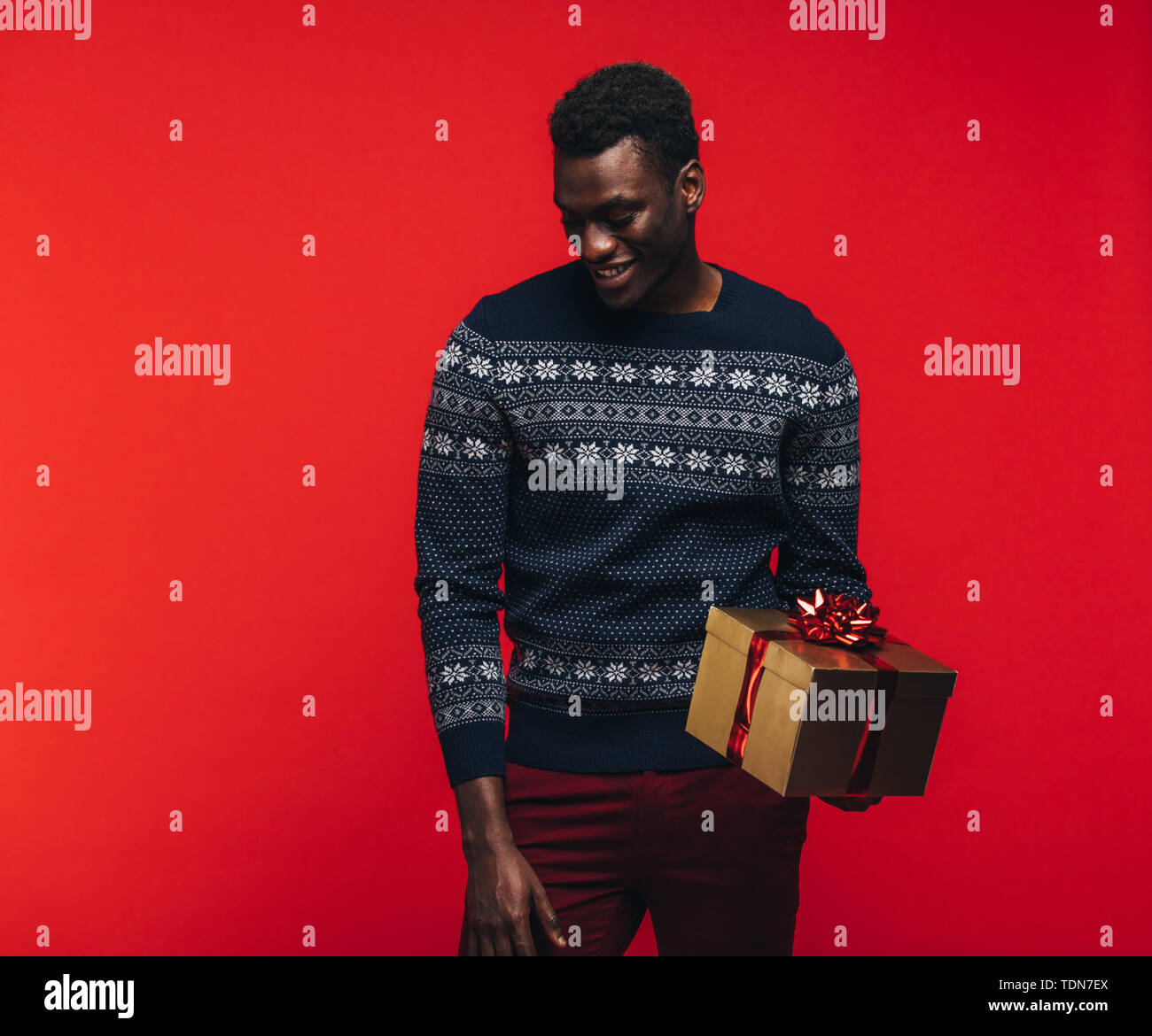 Young african guy holding a gift box. African american man with a present on red background. - Stock Image