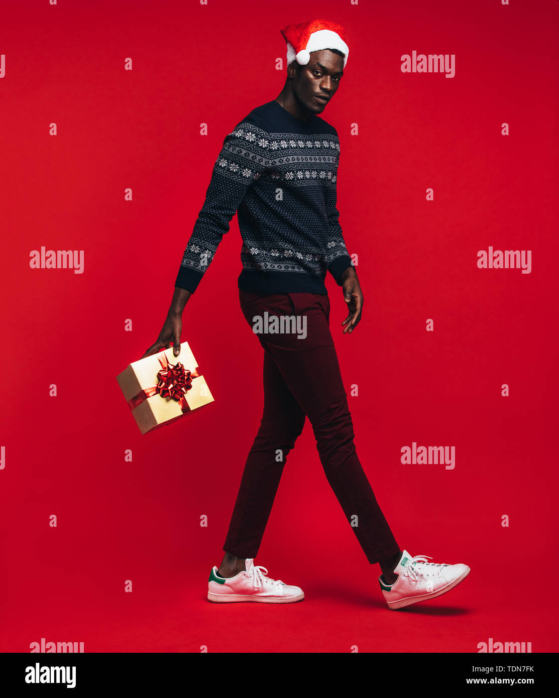 Young african man wearing santa hat jumping with gift box over red background. Handsome black guy with a christmas present on red background. - Stock Image