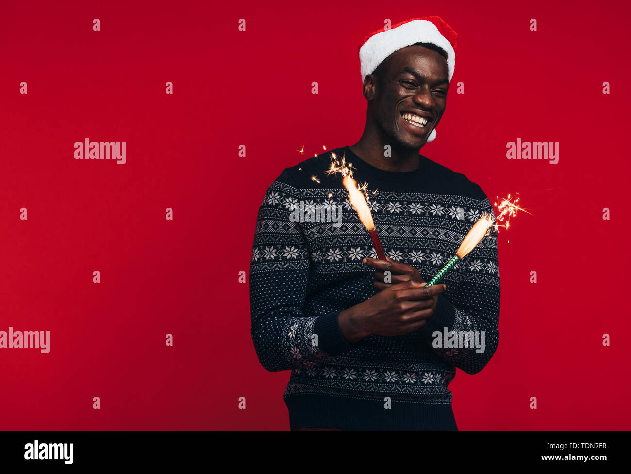 Cheerful young african man in santa hat celebrating with sparklers. Young guy enjoying with fireworks on red background - Stock Image