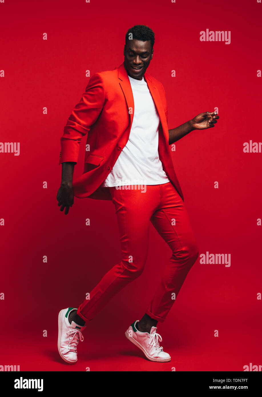 Full length od handsome young african man dancing on red background. Man in stylish red outfit showing some dance moves. - Stock Image