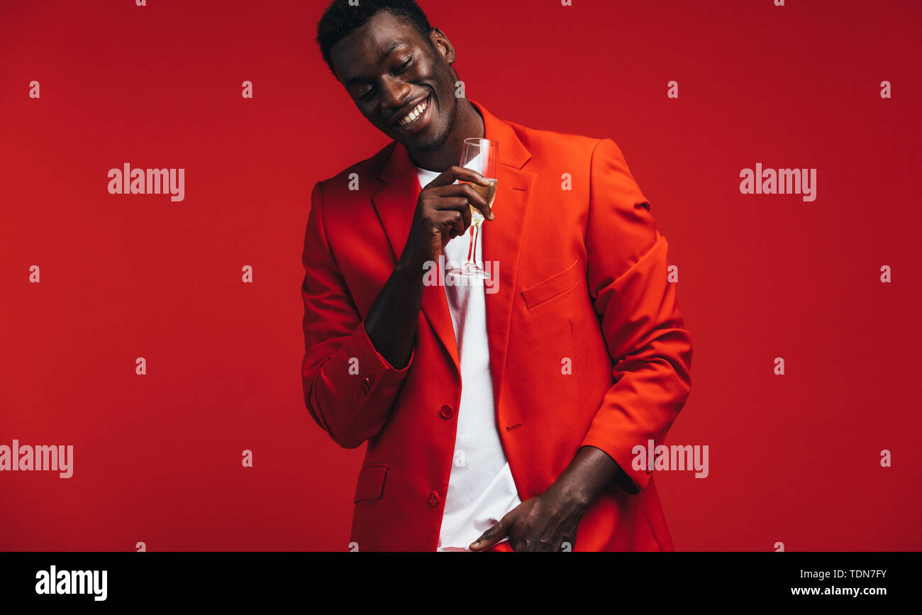 Cheerful young man in red jacket with a glass of champagne. Smiling african american man having a glass of champagne against red background. - Stock Image