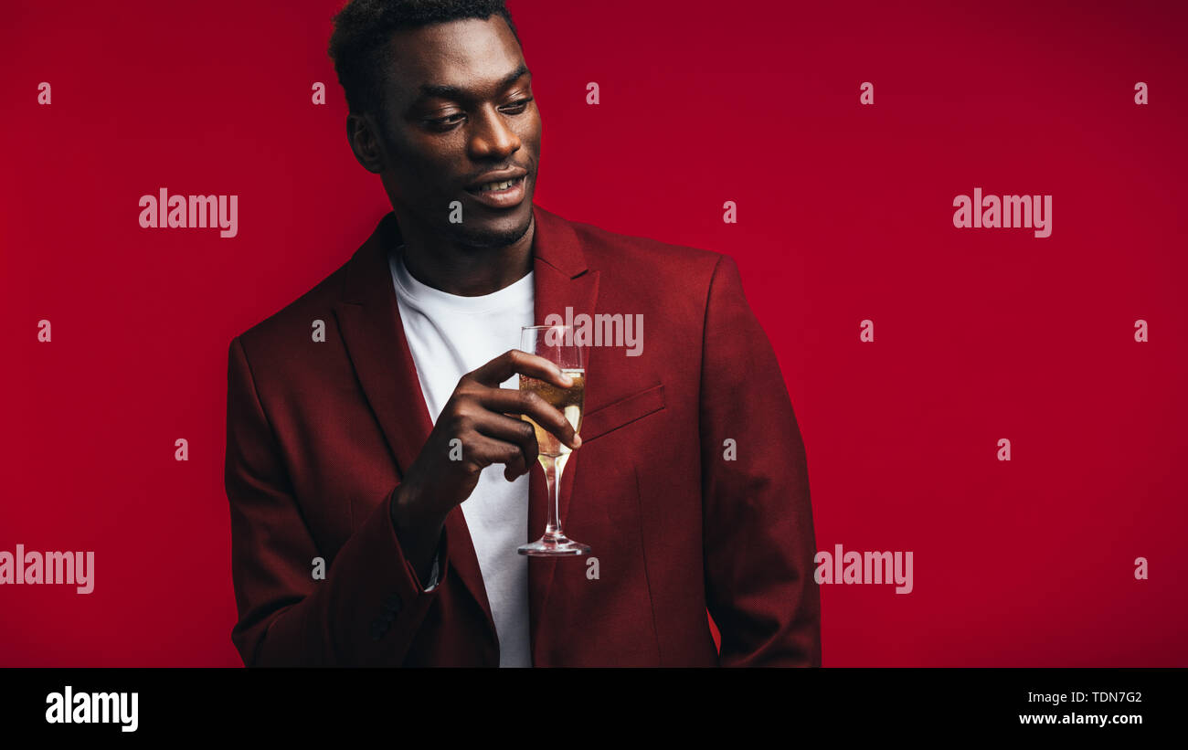Stylish african man with a glass of champagne looking away at copy space. Man in red jacket having champagne against colored background. - Stock Image
