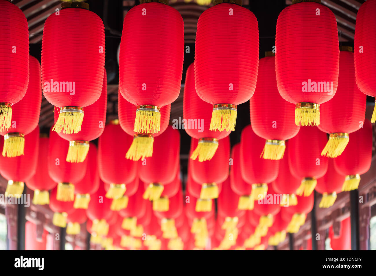 Red chinese lanterns hanging in a chinese bridge corridor close-up, Chengdu, China - Stock Image