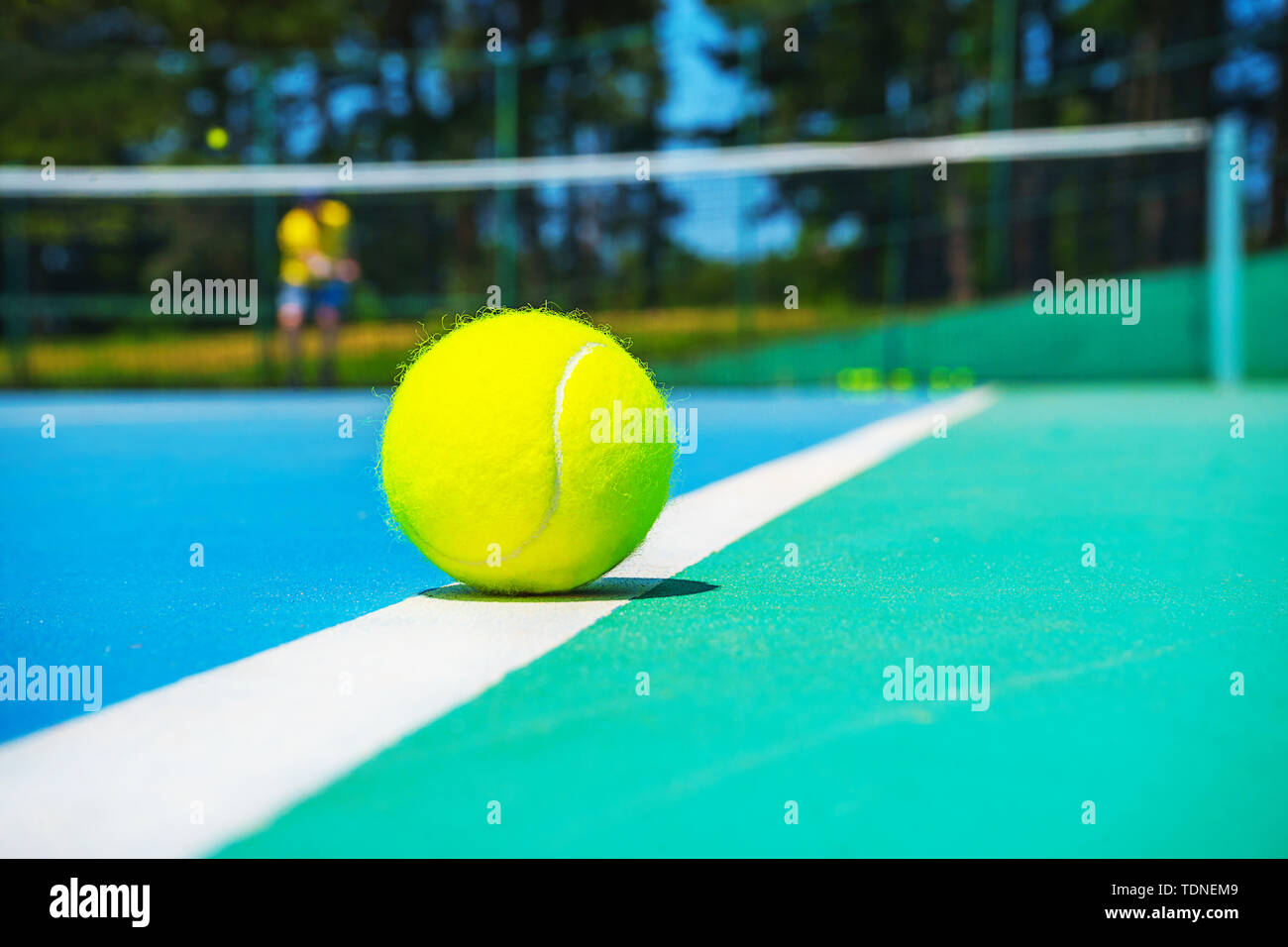 Tennis ball on white court line on hard modern blue green court with player, net, balls, trees on the background. Stock Photo