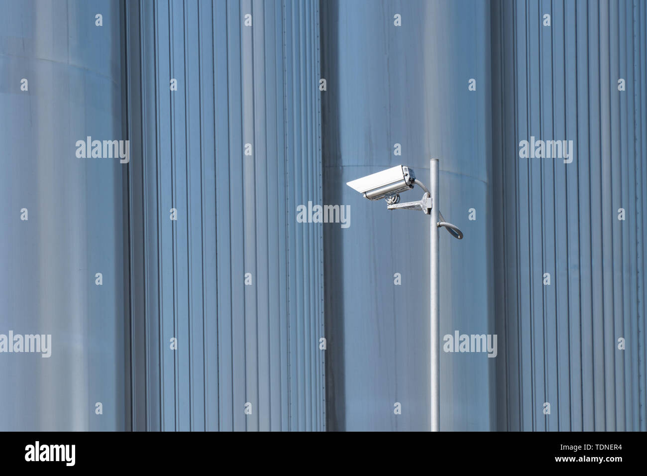 Security camera on metallic background. Surveillance on industrial spaces - Stock Image