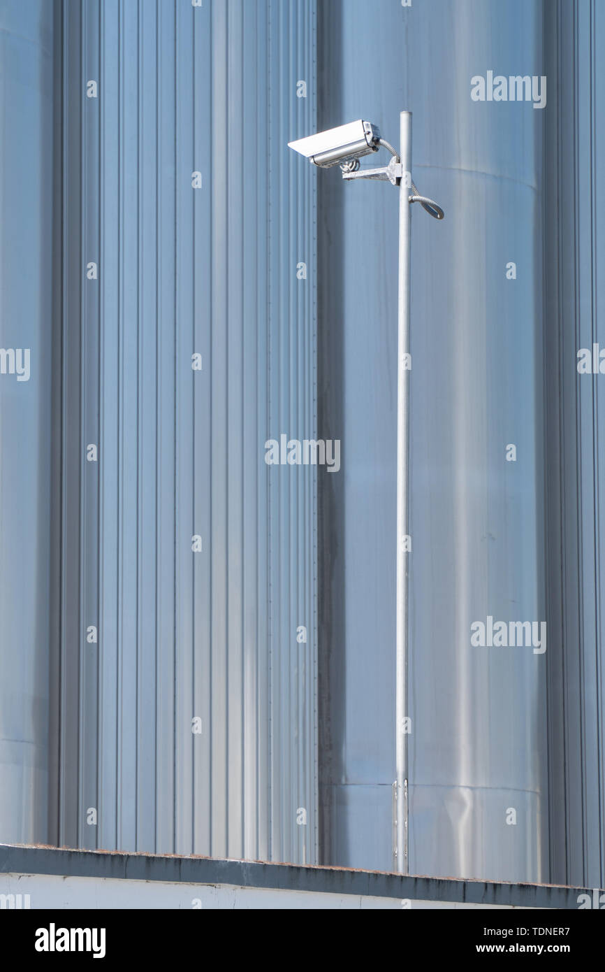 Security camera on metallic background. Surveillance on industrial spaces Stock Photo