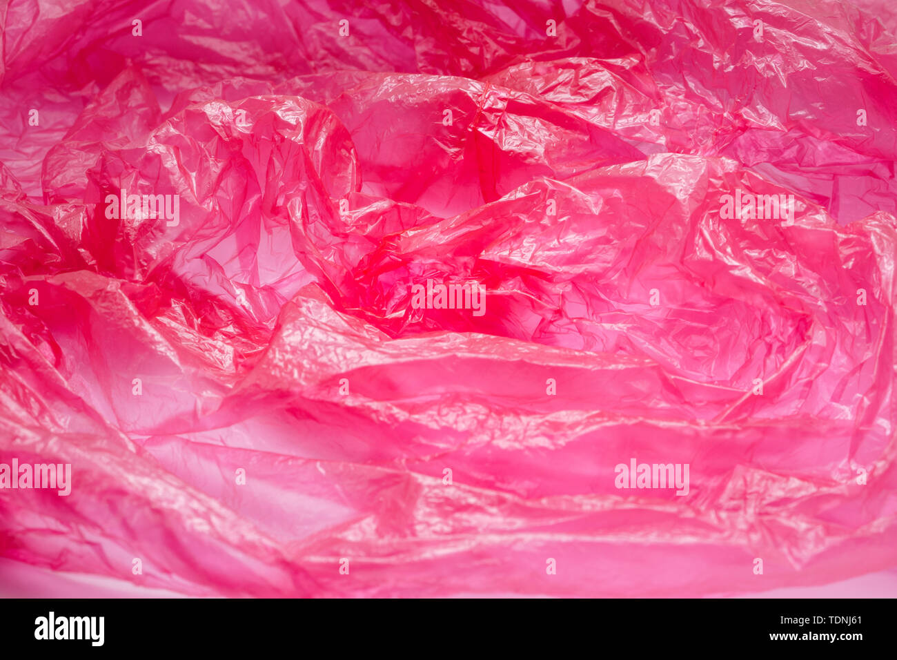 Red Plastic Bag Texture. Abstract Wrinkled Background of Plastic Garbage - Stock Image
